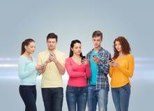 Grupa poważni nastolatkowie z smartphones Zdjęcia Royalty Free