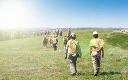 Grupa pracownicy chodzi trawy pole i sprawdza w hardhats fotografia stock