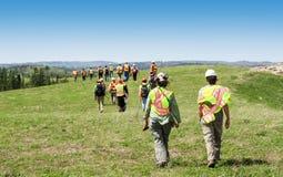 Grupa pracownicy chodzi trawy pole i sprawdza w hardhats zdjęcia royalty free