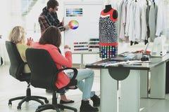 Grupa projektanci dyskutuje nową ubraniową kolekcję obraz royalty free