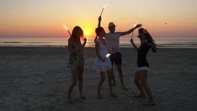 Grupa przyjaciele świętuje z sparklers przy plażą przy wschodem słońca zbiory