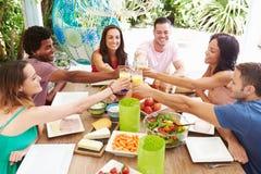 Grupa przyjaciele Cieszy się posiłek Outdoors W Domu zdjęcie royalty free