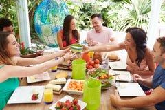 Grupa przyjaciele Cieszy się posiłek Outdoors W Domu fotografia stock