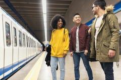 Grupa przyjaciele czeka pociąg w platformie stacja metru obrazy stock