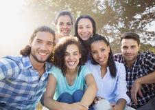 Grupa przyjaciele ono uśmiecha się w rozmytym parku zdjęcie royalty free