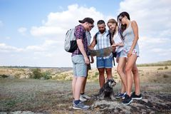 Grupa przyjaciele patrzeje mapę i dyskutuje outdoors Przyjaciele iść przy wycieczkować, las, odtwarzanie, miłość aktywnego styl ż Zdjęcia Stock