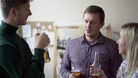 Grupa przyjaciele pije alkoholicznych napoje w biurze Butelkowy piwo Dorosłego napoju clink i piwo zbiory