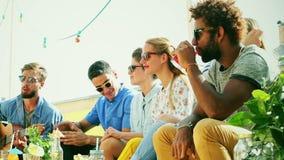 Grupa przyjaciele pije zabawę i ma przy dachu przyjęciem zbiory