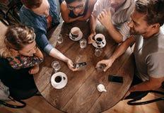 Grupa przyjaciele przy kawiarnią i patrzeć mądrze telefon Zdjęcia Royalty Free