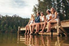 Grupa przyjaciele siedzi na jetty przy jeziorem Zdjęcia Stock