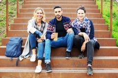 Grupa przyjaciele siedzi outside na schodkach obrazy stock