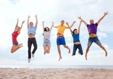 Grupa przyjaciele skacze na plaży Zdjęcia Royalty Free