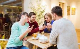 Grupa przyjaciele spotyka przy kawiarnią z smartphones Fotografia Royalty Free