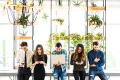Grupa przyjaciele stoi na stołowym i everyone use jego divices w nowożytnym biurowym pokoju Wpólnie zabawa w przyrządzie zdjęcia royalty free