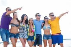 Grupa przyjaciele wskazuje gdzieś na plaży obraz royalty free