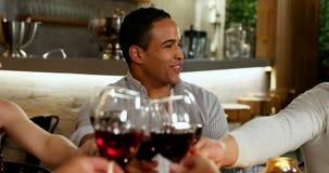 Grupa przyjaciele wznosi toast win szkła podczas gdy mieć gościa restauracji 4K 4k zbiory wideo