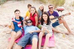 Grupa przyjaciele z gitarą ma zabawę na plaży Obrazy Royalty Free