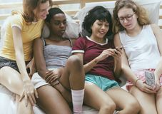 Grupa różnorodne kobiety kłama na łóżku używać telefon komórkowego wpólnie obraz stock