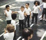 Grupa różnorodni dziecinów ucznie stoi w linii przy playg fotografia stock
