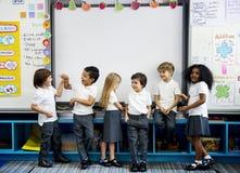 Grupa różnorodni dziecinów ucznie stoi wpólnie w clas obraz stock
