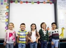 Grupa różnorodni dziecinów ucznie stoi wpólnie w clas fotografia stock
