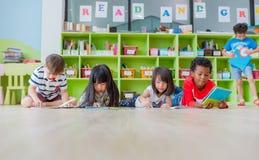 Grupa różnorodność dzieciak kłaść puszek na podłoga i czytelniczej bajki książce ja obraz stock