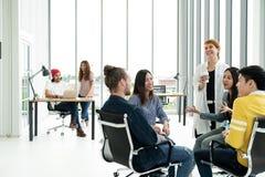 Grupa różnorodność ludzie, roześmiany i rozochocony w małym spotkaniu Zespalamy się uśmiecha się przy nowożytnym biurem, zdjęcie royalty free