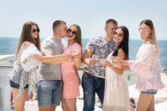 Grupa radośni przyjaciele relaksuje na wakacje Ładne dziewczyny i silni mężczyzna na niebieskiego nieba tle przyjaźń obrazy stock