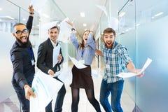 Grupa radośni z podnieceniem ludzie biznesu ma zabawę w biurze