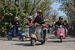 Grupa rowerzyści jedzie rocznik hulajnog Włoskiego Vespa i Lambretta fotografia royalty free