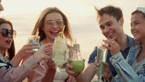 Grupa roześmiani ludzie otuch z napojami, clink szkła lato miastowy koktajl zdjęcie wideo