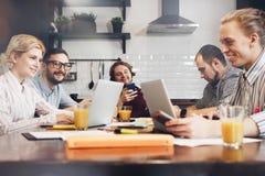 Grupa rozochoceni coworkers siedzi przy stołem z laptopami i pa obraz stock