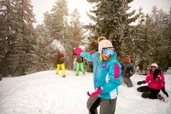 Grupa rozochoceni przyjaciele ma śnieżnego bój i zabawę w śnieżnym zdjęcie royalty free
