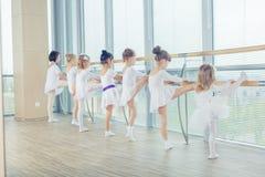 Grupa siedem małych balerin stoi w rzędzie i ćwiczyć Fotografia Stock