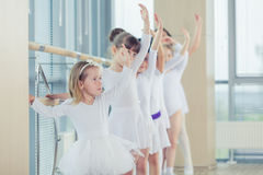 Grupa siedem małych balerin stoi w rzędzie i ćwiczy balecie używać kij na ścianie Zdjęcie Royalty Free