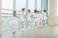 Grupa siedem małych balerin stoi w rzędzie i ćwiczy balecie używać kij na ścianie Obrazy Royalty Free