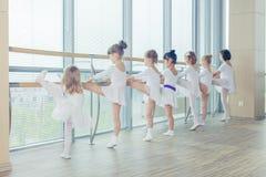 Grupa siedem małych balerin stoi w rzędzie i ćwiczy balecie używać kij na ścianie Zdjęcie Stock