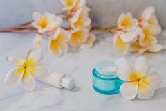 Grupa skincare produkty wliczając moisturiser i ręki śmietanki garnków na marmuru stole z egzotycznym frangipani kwitnie obrazy royalty free