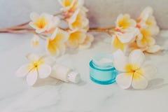 Grupa skincare produkty wliczając moisturiser i ręki śmietanki garnków na marmuru stole z egzotycznym frangipani kwitnie zdjęcie stock
