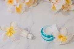 Grupa skincare produkty wliczając moisturiser i ręki śmietanki garnków na marmuru stole z egzotycznym frangipani kwitnie obrazy stock