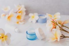 Grupa skincare produkty wliczając moisturiser ręki i pętaczki śmietanki garnków na marmuru stole z egzotycznym frangipani kwitnie zdjęcie stock