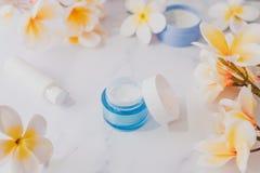 Grupa skincare produkty wliczając moisturiser ręki i pętaczki śmietanki garnków na marmuru stole z egzotycznym frangipani kwitnie fotografia stock