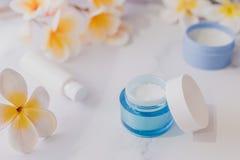 Grupa skincare produkty wliczając moisturiser ręki i pętaczki śmietanki garnków na marmuru stole z egzotycznym frangipani kwitnie zdjęcia royalty free