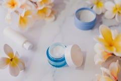 Grupa skincare produkty wliczając moisturiser ręki i pętaczki śmietanki garnków na marmuru stole z egzotycznym frangipani kwitnie zdjęcia stock