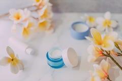 Grupa skincare produkty wliczając moisturiser ręki i pętaczki śmietanki garnków na marmuru stole z egzotycznym frangipani kwitnie obrazy royalty free