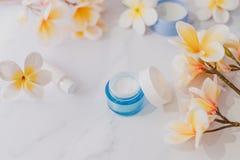 Grupa skincare produkty wliczając moisturiser ręki i pętaczki śmietanki garnków na marmuru stole z egzotycznym frangipani kwitnie obrazy stock
