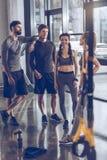 Grupa sportowi młodzi ludzie w sportswear odpoczywać przy gym i pozyci fotografia royalty free