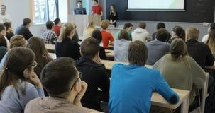 Grupa studenci uniwersytetu siedzi przy ich biurkami w audytorium i słuchaniem jako ich nauczyciel trzyma wykład zbiory wideo