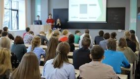 Grupa studenci uniwersytetu siedzi przy ich biurkami w audytorium i słuchaniem jako ich nauczyciel trzyma wykład zdjęcie wideo