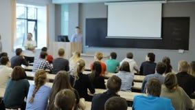 Grupa studenci uniwersytetu siedzi przy ich biurkami w audytorium i słuchaniem jako ich nauczyciel trzyma wykład zbiory